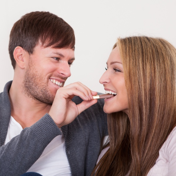 Young man feeding chocolate bar to his girlfriend at home