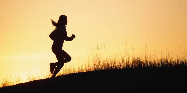 Silhouette of woman running up hill